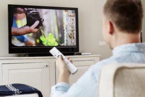 Man håller upp en fjärrkontrol framför en tv.