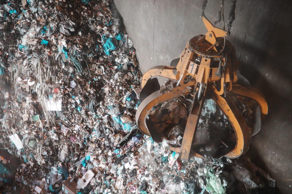 Klo lyfter upp påsar med hushållssopor i Skövde Energis verksamhet.